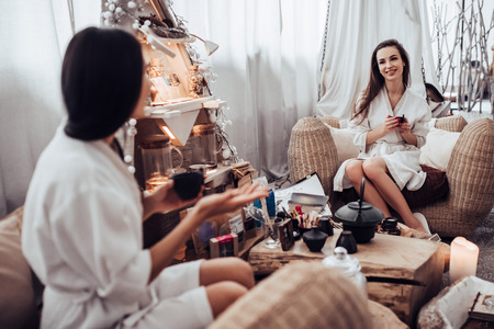 Two young women are relaxing in spa and wellness center together. Talking and drinking tea.