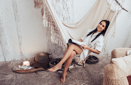Attractive young woman is relaxing in spa and wellness center. Beauty treatment concept. Reading journal while lying in hammock