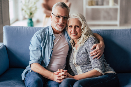 Love lives forever! Senior couple at home. Handsome old man and attractive old woman are spending time together. Sitting on a sofa, hugging and holding hands. 스톡 콘텐츠