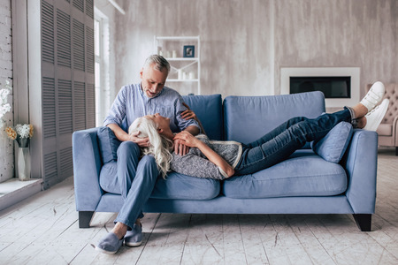 Love lives forever! Senior couple at home. Handsome old man and attractive old woman are hugging and enjoying spending time together. Man is sitting on sofa while woman is lying on his knees.