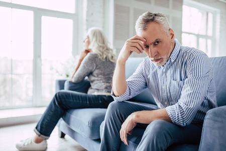 Senior koppel thuis. Knappe oude man en aantrekkelijke oude vrouw hebben relatieproblemen. Samen op de bank zitten en naar tegenovergestelde kanten kijken.