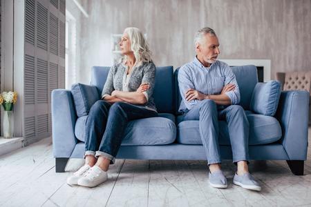 自宅でシニアカップル。ハンサムな老人と魅力的なおばあは、関係の問題を抱えています。一緒にソファに座って、反対側を見て。