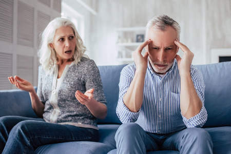 Senior couple at home. Handsome old man and attractive old woman are having relationship problems. Sitting on sofa together while quarrel.