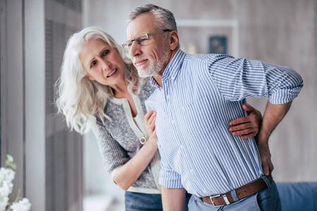 Altes Paar zu Hause. Gut aussehender alter Mann hat Rückenschmerzen und seine attraktive alte Frau unterstützt ihn.