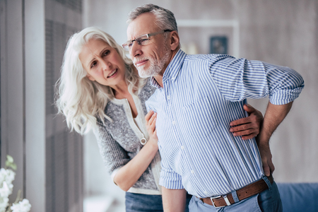 Senior couple at home. Handsome old man is having back pain and his attractive old woman supports him. Stockfoto