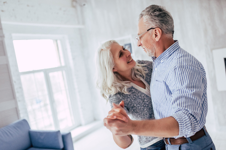 Love lives forever! Senior couple at home. Handsome old man and attractive old woman are enjoying spending time together while dancing. Archivio Fotografico