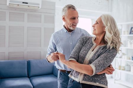 ¡El amor vive por siempre! Senior pareja en casa. Apuesto anciano y atractiva anciana están disfrutando pasar tiempo juntos mientras bailan. Foto de archivo