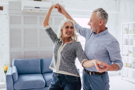 愛は永遠に生きる!自宅でシニアカップル。ハンサムな老人と魅力的なおばあは、ダンスをしながら一緒に過ごす時間を楽しんでいます。