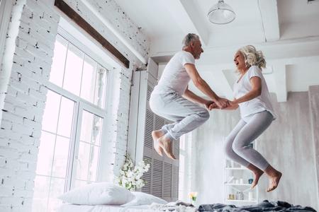 ¡El amor vive por siempre! Senior pareja en casa. Apuesto anciano y atractiva anciana están disfrutando pasar tiempo juntos. Divirtiéndose y saltando en la cama. Foto de archivo