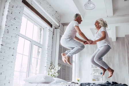 L'amour vit pour toujours! Couple de personnes âgées à la maison. Beau vieillard et jolie vieille femme aiment passer du temps ensemble. S'amuser et sauter dans son lit. Banque d'images