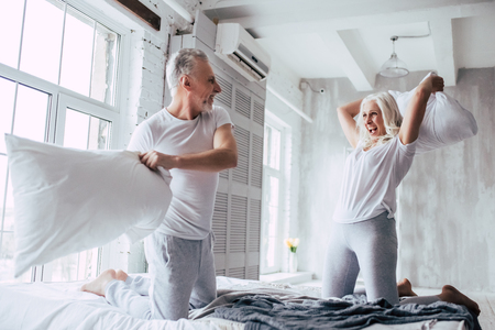 Love lives forever! Senior couple at home. Handsome old man and attractive old woman are enjoying spending time together. Having fun while having pillows battle.
