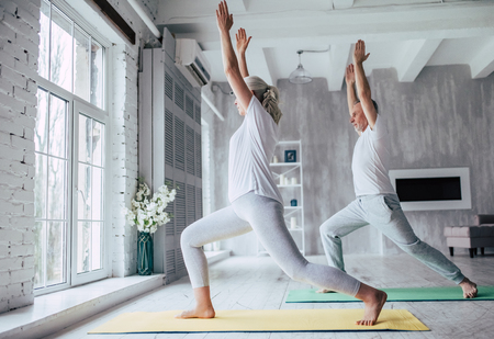 Senior couple is doing fitness training at home. Doing yoga together. Healthy lifestyle concept. Foto de archivo