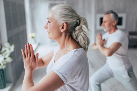 Senior couple is doing fitness training at home. Doing yoga together. Healthy lifestyle concept. Stok Fotoğraf