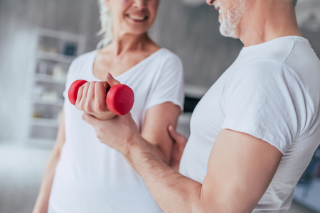 Senior couple is doing fitness training at home. Attractive old woman is standing with dumbbells while handsome old man helps and supports her.
