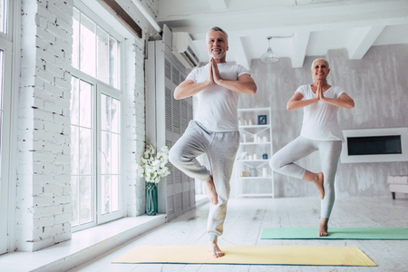 Senior couple is doing fitness training at home. Doing yoga together. Healthy lifestyle concept. Archivio Fotografico