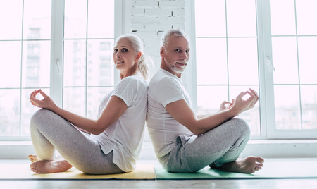 Senior couple is doing fitness training at home. Doing yoga together. Healthy lifestyle concept. Stock Photo
