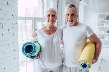 Lteres Paar tut Eignung, die zu Hause ausbildet. Stehen mit Eignungsyogateppichen. Gesundes Lebensstilkonzept. Standard-Bild - 98231572
