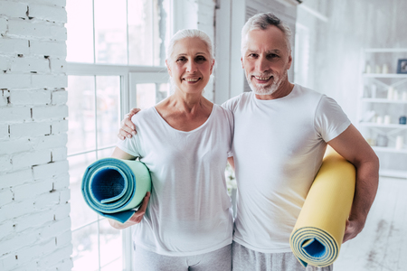 Senior pareja está haciendo entrenamiento físico en casa. De pie con alfombras de yoga fitness. Concepto de estilo de vida saludable