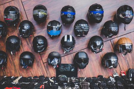 Motorfietsen en accessoires in moderne motorfietswinkel. Biker spullen. Helmen op houten achtergrond.