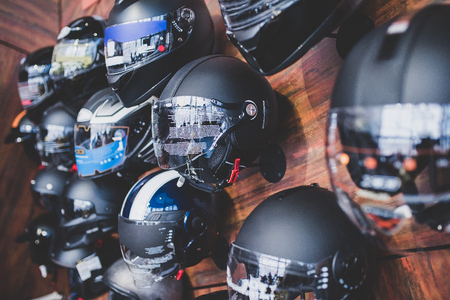 Motorcycles and accessories in modern motorcycle shop. Biker stuff. Helmets on wooden background. Фото со стока - 98373353