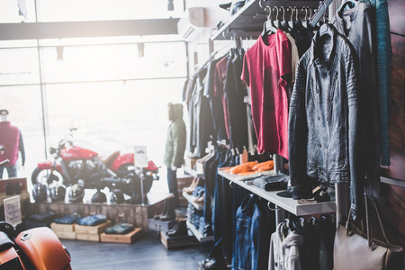 Motorcycles and accessories in modern motorcycle shop. Biker stuff and clothes.
