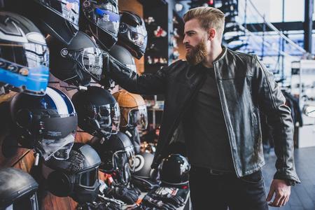 オートバイの店でハンサムなひげを生やした男。バイカーは、新しい車両やオートバイのアクセサリーを選択しています。木製の背景にヘルメット