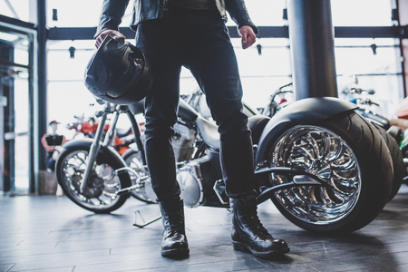 Handsome bearded man in motorcycle shop. Biker is choosing new vehicle and motorcycle accessories. Cropped image of man standing with helmet. Safety driving concept.