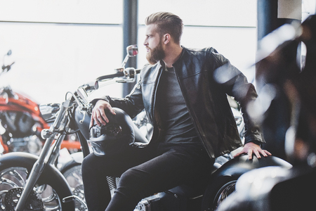 Handsome bearded man in motorcycle shop. Biker is choosing new vehicle and motorcycle accessories. Cropped image of man sittiing with helmet. Safety driving concept.