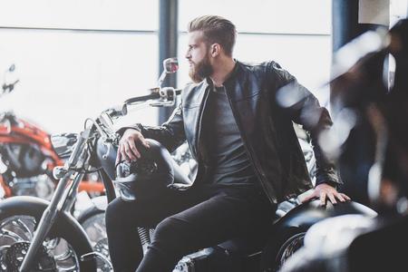 Hübscher bärtiger Mann im Motorradshop. Radfahrer wählt neues Fahrzeug- und Motorradzubehör. Zugeschnittenes Bild des Mannes sitzend mit Sturzhelm. Sicherheitskonzept.