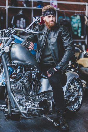 Handsome bearded man in motorcycle shop. Biker is choosing new vehicle and motorcycle accessories while sitting on new bike.