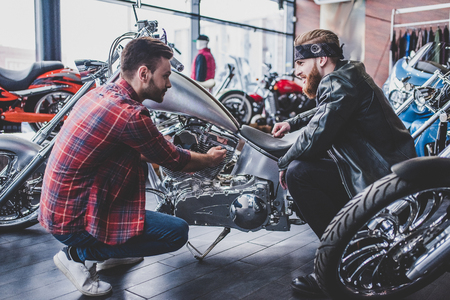 Two men in motorcycle shop. Customer and salesman. Shop assistant is helping bearded man in choosing new vehicle, motorcycle accessories and other biker stuff. Standard-Bild
