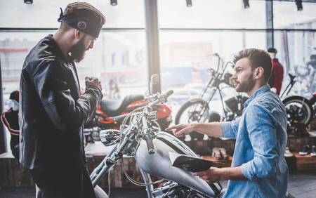Two men in motorcycle shop. Customer and salesman. Shop assistant is helping bearded man in choosing new vehicle, motorcycle accessories and other biker stuff. Archivio Fotografico