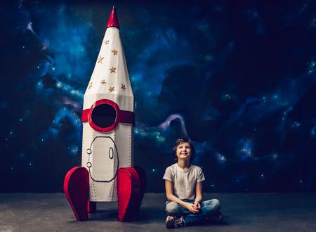 Il ragazzo è seduto vicino al razzo giocattolo sullo sfondo dello spazio.