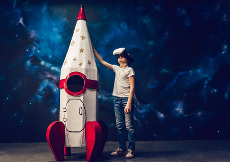 Boy is standing near toy rocket on space background and wearing glasses of virtual reality.