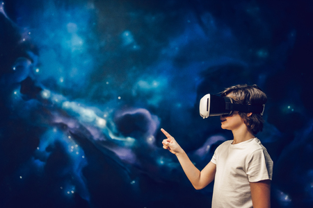 Little boy wearing glasses of virtual reality on space background.