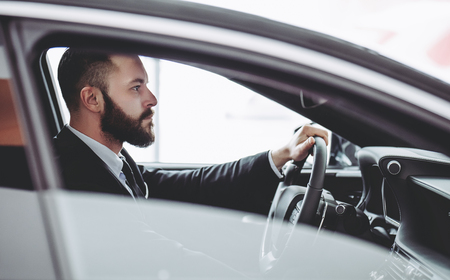 Young handsome businessman is sitting in luxury car. Serious bearded man in suit is driving.