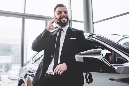 Young handsome businessman in suit is standing near car and talking on smart phone.
