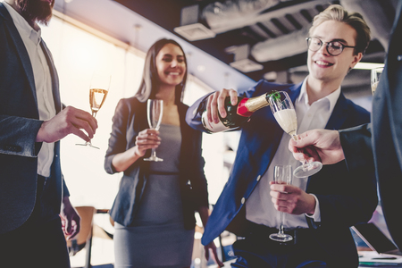 Group of young business people are working together in modern office. Successful team in coworking are celebrating event with champagne. Freelancers.