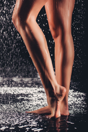 Cropped image of sexy woman in shower. Attractive young naked woman under water drops isolated on black background. Close-up of womans legs. 写真素材