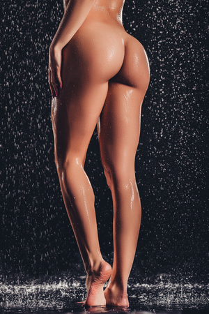 Cropped image of sexy woman in shower. Attractive young naked woman under water drops isolated on black background. Close-up of womans legs and buttocks.