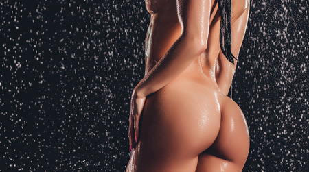 Cropped image of sexy woman in shower. Attractive young naked woman under water drops isolated on black background. Close-up of womans buttocks.