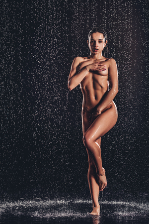 Full-length image of sexy woman in shower. Attractive young naked woman under water drops isolated on black background.