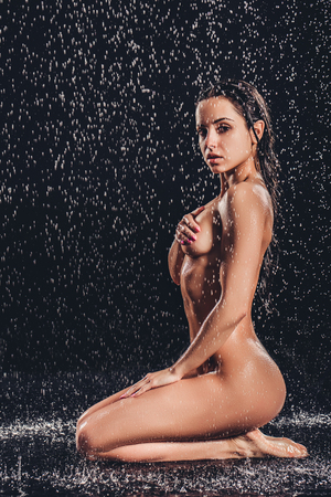 Sexy woman in shower. Attractive young naked woman under water drops isolated on black background.