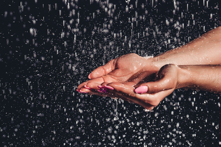 Cropped image of woman in shower. Close-up of womans hands under the water drops. Hands isolated on black background.