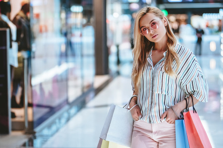 Attractive young happy woman is doing shopping with shopping bags in modern mall. 写真素材