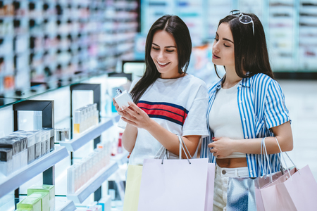 Two attractive young girls are doing shopping with shopping bags in perfume store in modern mall.