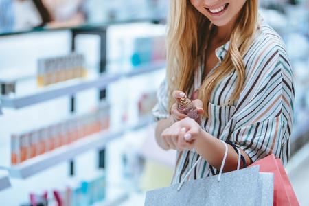 Przycięty obraz atrakcyjnej młodej dziewczyny robi zakupy z torby na zakupy w perfumerii w nowoczesnym centrum handlowym. Zdjęcie Seryjne