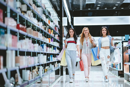 Three attractive young girls are doing shopping with shopping bags in modern mall.