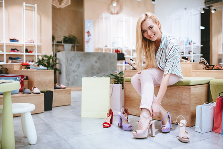 Attractive young girl is doing shopping with shopping bags in shoes store in modern mall. Imagens