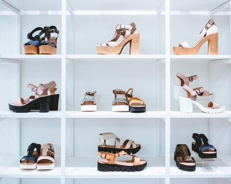 White rack in shoes store. Different kinds of women shoes are on sale in modern shoes store.